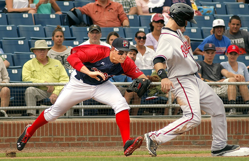 Third baseman Garin Cecchini of the Portland Sea Dogs swipes at Ryan Lollis of the Richmond Flying Squirrels, who hustled back after advancing on a single.