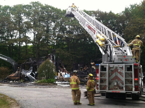 Firefighters continue to work at what is left of Wescustogo Hall in North Yarmouth on Friday morning.