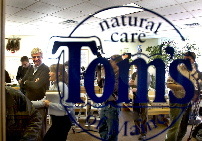 In this March 2006 file photo, founder Tom Chappell is seen through the Kennebunk Outlet store window for Tom's of Maine. Tom's of Maine, the widely known producer of all-natural personal care products, is eliminating 28 jobs nationally as it changes its sales and marketing teams.