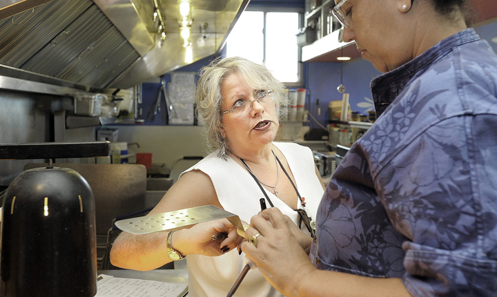 Portland health inspector Michele Sturgeon goes through the kitchen at El Rayo Taqueria on Monday, September 24, 2012 with executive chef Cheryl Lewis.