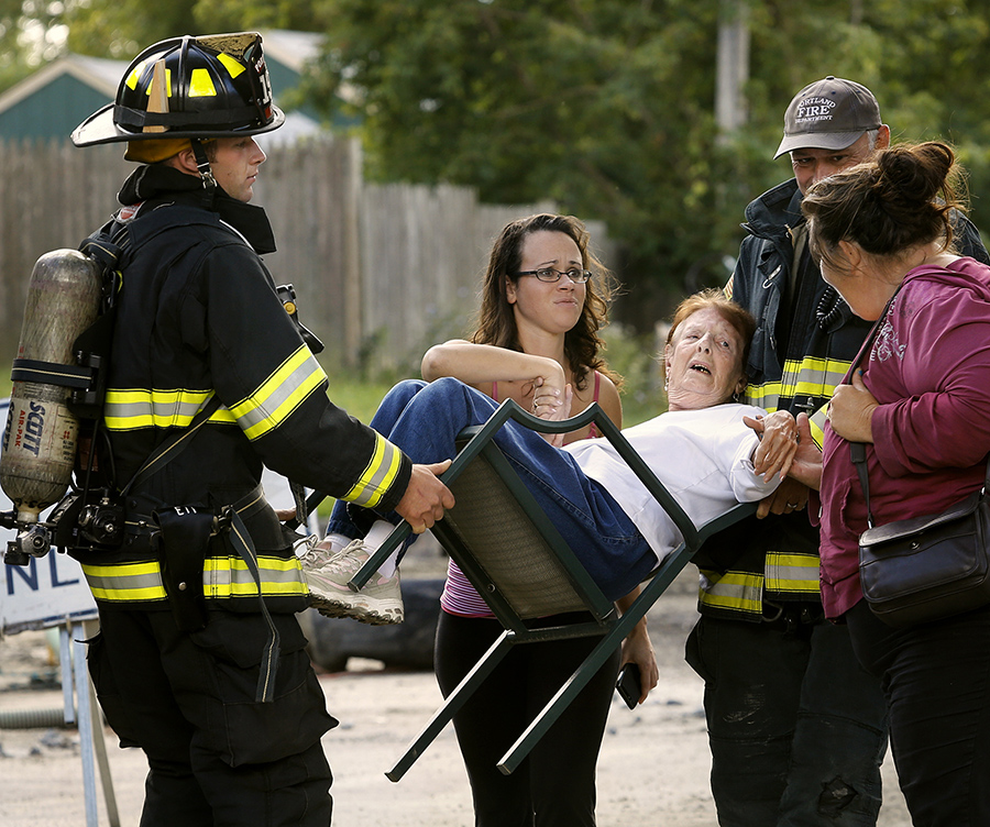 Catherine Lock of 120 Front Street is carried along Johansen Street by Josh Tripp, left, and Sean Meehan after a gas line break caused Portland firefighters to evacuate residents from the area. Also pictured are Lock's neighbors Becca Randall and Patty Fitsimmons, right. Photographed on September 5, 2013.
