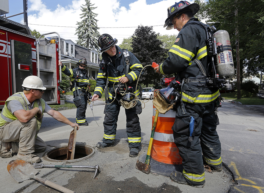 Portland firefighters Mike Scherb, right, and Travis Gibson test a manhole after a gas line break on Front Street in Portland. Photographed on September 5, 2013.