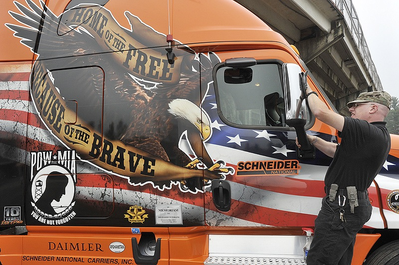 Richard Barczewski, a truck driver for Schneider National trucking, polishes his specially painted truck before the ceremonies at The Ballpark to honor prisoners of war and servicemen missing in action. Schneider National has six similarly painted trucks in its fleet that are driven by veterans only.