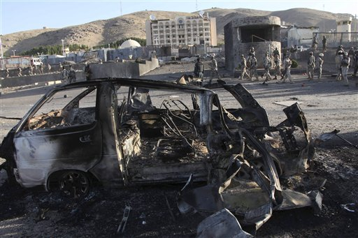 Afghan security personnel investigate the site of a suicide car bombing and a gunfight near the U.S. consulate (building in background) in Herat Province, west of Kabul, on Friday.