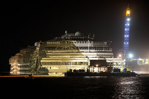 """The Costa Concordia is seen after it was lifted upright, on the Tuscan Island of Giglio, Italy, early Tuesday morning. The crippled cruise ship was pulled completely upright early Tuesday after a complicated, 19-hour operation to wrench it from its side where it capsized last year off Tuscany, with officials declaring it a """"perfect"""" end to a daring and unprecedented engineering feat."""