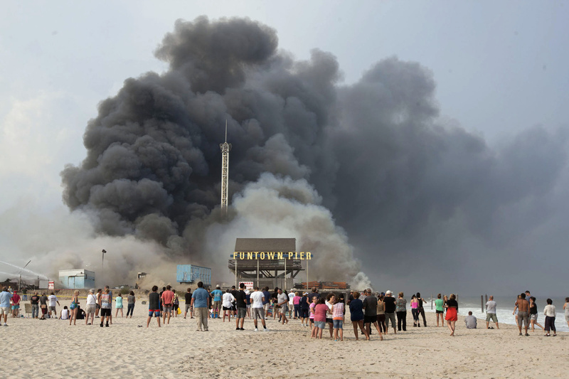 Onlookers watch from the shore as black smoke rises from a fire on the Seaside Heights, N.J., boardwalk. The fire started in the vicinity of an ice cream shop and burned several blocks of boardwalk and businesses in a town that was still rebuilding from damage caused by superstorm Sandy.