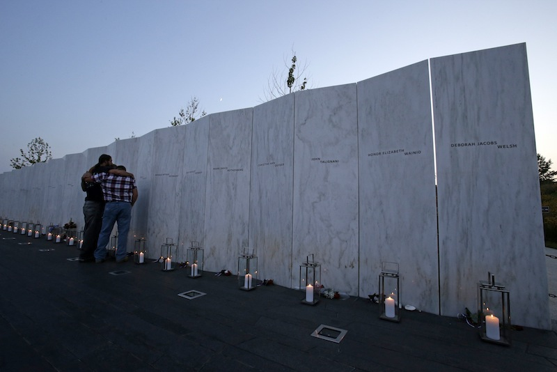 Visitors embrace in front of the wall containing the 40 names of the crew and passengers of Flight 93 at the Flight 93 National Memorial during a candlelight remembrance on Tuesday, September 10, 2013. (AP Photo/Gene J. Puskar)