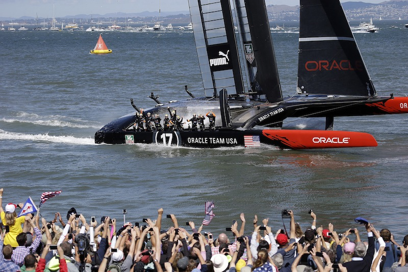 The crew on Oracle Team USA celebrates after winning the 19th race against Emirates Team New Zealand to win the America's Cup sailing event, as fans wave in the foreground Wednesday, Sept. 25, 2013, in San Francisco.