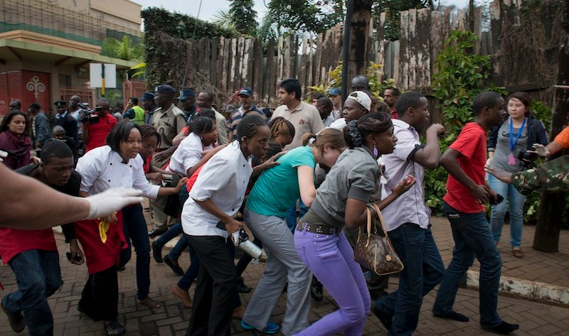 Civilians who had been hiding inside during the gun battle manage to flee from the Westgate Mall in Nairobi, Kenya Saturday, Sept. 21, 2013. Gunmen threw grenades and opened fire Saturday, killing at least 22 people in an attack targeting non-Muslims at an upscale mall in Kenya's capital that was hosting a children's day event, a Red Cross official and witnesses said. (AP Photo/Jonathan Kalan)