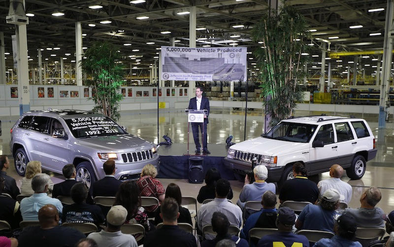 In this Aug. 13, 2013 file photo, Scott Garberding, senior vice president of manufacturing for Chrysler Group LLC stands between a 1992 Grand Cherokee, right, and the automaker's 5,000,000th vehicle produced at the Jefferson North Assembly Plant in Detroit. Chrysler's U.S. sales rose 12 percent in August as strong truck sales pushed the company to its best month in six years. (AP Photo/Carlos Osorio, File)