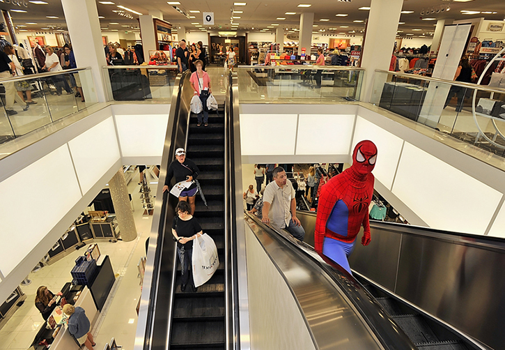 Shoppers take the down escalator with bags of purchases while a costumed Spider-Man heads up to the children's department on the second floor as Bon-Ton holds its grand opening at the Maine Mall on Thursday.