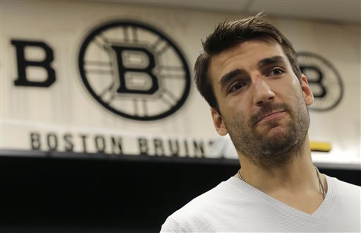 Boston Bruins center Patrice Bergeron talks with reporters in the team locker room, Tuesday, July 2, 2013, in Boston. The Bruins opened training camp Wednesday with only two roster spots seemingly uncertain, and those were on the third and fourth lines. (AP Photo/Charles Krupa)