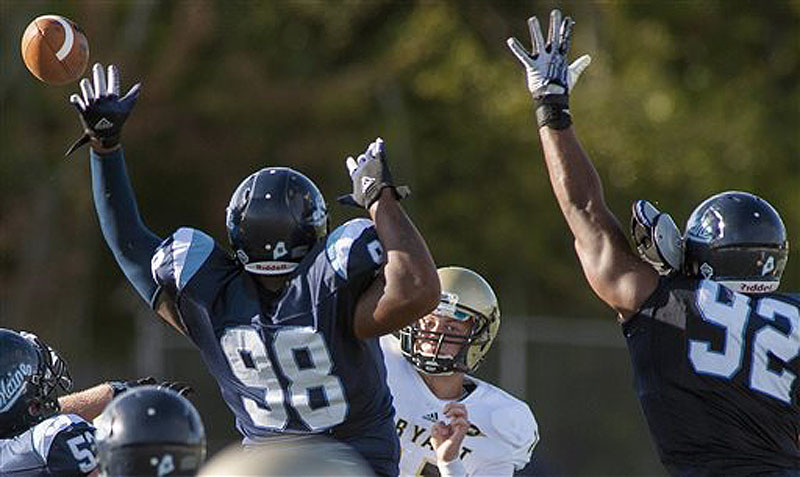 Maine football players Darius Greene (98) and Trevor Bates (92) try to block a pass from Bryant quarterback Mike Westerhaus in the first half Saturday.