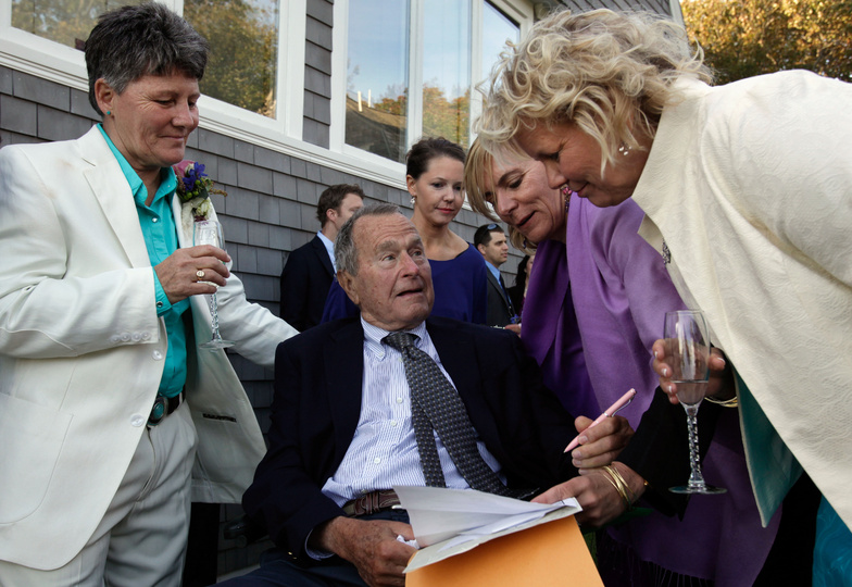 Former President George H.W. Bush prepares to sign the marriage license of longtime friends Helen Thorgalsen, right, and Bonnie Clement, left, in Kennebunkport, as officiant Nancy Sosa, third right, and Helen's daughter Lindsey, rear, look on in this May 22, 2014, photo. Bush was an official witness at the same-sex wedding, his spokesman said.