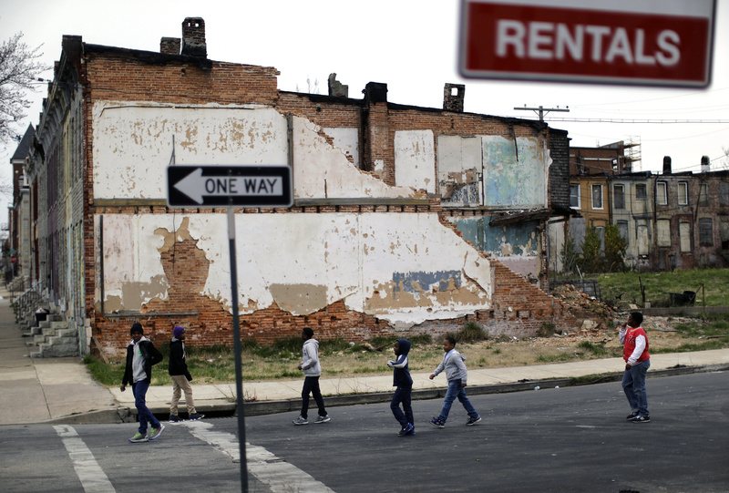 A group of boys walks past a partially collapsed row house in Baltimore. The nation's poverty rate stood still at 15 percent in 2012, the sixth straight year that it has failed to improve.