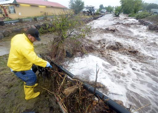 Trent Fallica of the City of Boulder Traffic Signal Department checks on an electrical box next to a raging creek during the flood in North Boulder, Colo., on Thursday.