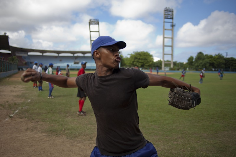 A baseball player who plays for the Cuban baseball team Industriales, winds up to throw a ball during a training session in Havana, Cuba, Friday, Sept. 27, 2013. Cuba announced Friday that its athletes will be allowed to sign contracts to compete in foreign leagues, a shift from decades of policy that held professional sports to be anathema to socialist ideals. The measure promises to increase the amount of money baseball players and others are able to earn, and seems geared toward stemming a continuing wave of defections by athletes who are lured abroad by the possibility of lucrative contracts, sapping talent from national squads. (AP Photo/Ramon Espinosa)