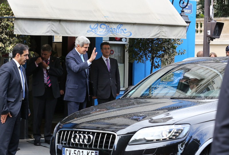 U.S. Secretary of State John Kerry waves a goodbye to Saudi foreign minister Prince Saud Al-Faisal Bin Abdul Aziz, unseen, in his car, right, following their working lunch in a Paris restaurant, Monday Sept. 16, 2013. The U.S. and its closest allies laid out a two-pronged approach in Syria on Monday, calling for enforceable U.N. benchmarks for eradicating the country's chemical weapons program and an international conference bolstering the moderate opposition. (AP Photo/Remy de la Mauviniere)