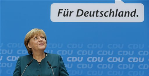 German Chancellor and chairwoman of the Christian Democratic party, CDU, Angela Merkel, smiles as she arrives for a news conference after a party's board meeting in Berlin, Monday, Sept. 23, 2013. German Chancellor Angela Merkel may have won an impressive third general election but she faces a delicate and lengthy task in forming a new government as party leaders met Monday to map out their next steps. Merkel's Union bloc achieved its best result in 23 years Sunday to put her on course for a third term, winning 41.5 percent of the vote and finishing only five seats short of an absolute majority in the lower house. However, Merkel's pro-business coalition partner since 2009 crashed out of Parliament. Words read: For Germany. (AP Photo/Matthias Schrader)