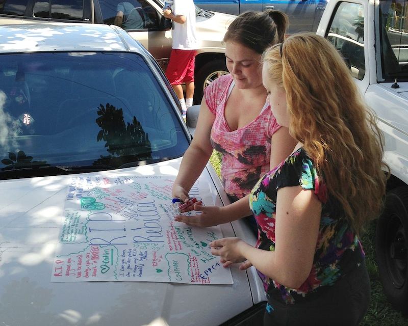 Summer Howard, 19, and Alecia Wilkins, 18, make a poster for Summer's sister, Rebecca Sedwick. Polk County Sheriff Grady Judd said that Sedwick jumped to her death Monday at an old cement business in Lakeland, Fla. Officials are looking into whether they can file charges under a new Florida state law that covers cyber-bullying.