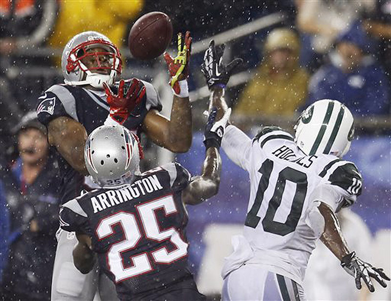 Patriots cornerback Aqib Talib, left, intercepts a pass intended for Jets wide receiver Santonio Holmes (10) in front of Patriots cornerback Kyle Arrington (25) in the fourth quarter Sept. 12 in Foxborough, Mass.