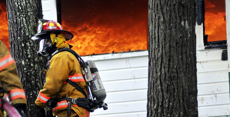 A firefighter approaches Echo Lake Lodge Tuesday in Fayette as it is destroyed by fire.