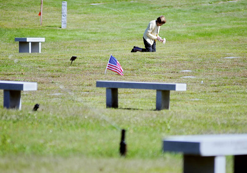 Betty Marchant places flowers Monday September 9, 2013 on the plots of her brother and sister-in-law at the Maine Veterans Memorial Cemetery in Augusta.