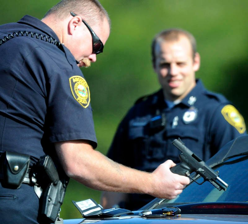 Augusta Police Department Sgt. Christopher Shaw inspects a pistol that officers briefly took from a man Tuesday following a road-rage incident in Augusta.