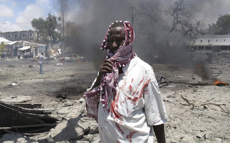 In this October 2011 file photo, a wounded man stands at the scene of an explosion in Mogadishu, Somalia in which 55 people were killed after the al-Shabab set off a car full of explosives in front of the Ministry of Education. The Islamic extremist group claiming responsibility for the weekend terrorist attack at a Kenyan mall presents a threat not just to the region or Africa but to the world at large, the president of Somalia said Monday on a trip to Ohio. (AP Photo/Mohamed Sheikh Nor, file)