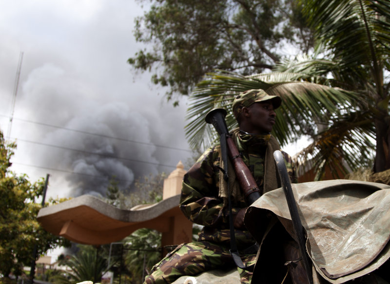 A soldier holds a RPG near the Westgate shopping mall in Nairobi, Kenya, as smoke rises from it, Monday Sept 23 2013. Islamic extremist gunmen lobbed grenades and fired assault rifles inside Nairobi's top mall Saturday, killing dozens and wounding over a hundred in the attack. A day after a Twitter post linked Maine to Saturday's terrorist attack in a mall in Nairobi, Kenya, law enforcement officials refused to say whether they are investigating the possibility that radical Islamist groups are trying to recruit new members in the state. (AP Photo/ Sayyid Azim)