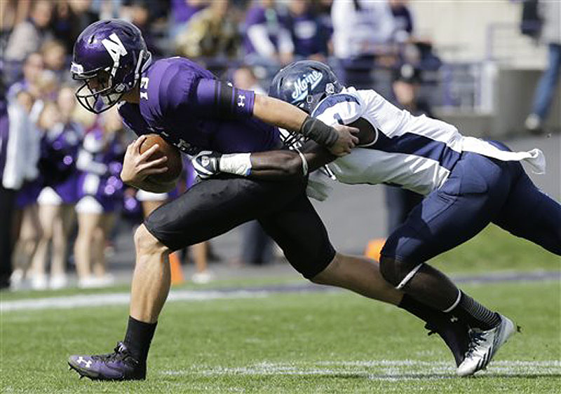 Maine defensive back Axel Ofori Jr. tackles Northwestern cornerback C.J. Bryant (13) during the first quarter of their game in Evanston, Ill., on Saturday. Northwestern won, 35-21