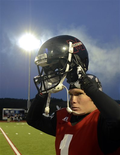 Mansfield University's Kirk Haskill is illuminated by the lights as he puts on his helmet prior to a college sprint football game against Princeton in Mansfield, Pa. on Saturday. The game marks the first time that Mansfield has held an official night football game since 1892, when Mansfield staged the first-ever night football game.