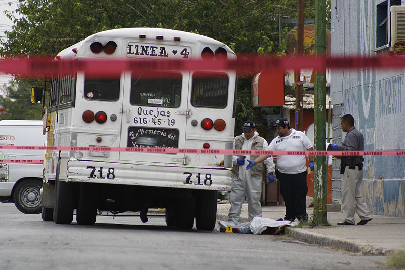 """Forensic workers examine the scene where a bus driver was allegedly killed by a self-styled """"bus driver hunter"""" in Ciudad Juarez, Mexico, on Aug. 28."""