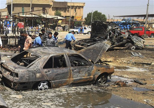 Iraqi security forces inspect the site of a car bomb attack in Basra Sunday.