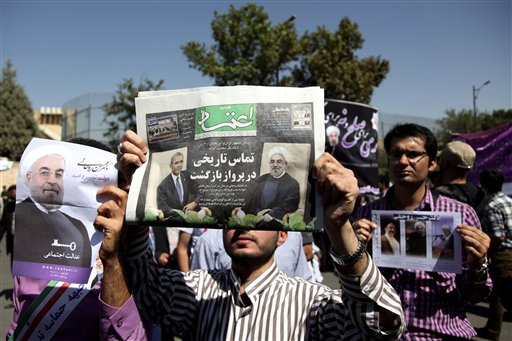 A supporter of Iranian President Hassan Rouhani holds a local newspaper with a headline that reads,