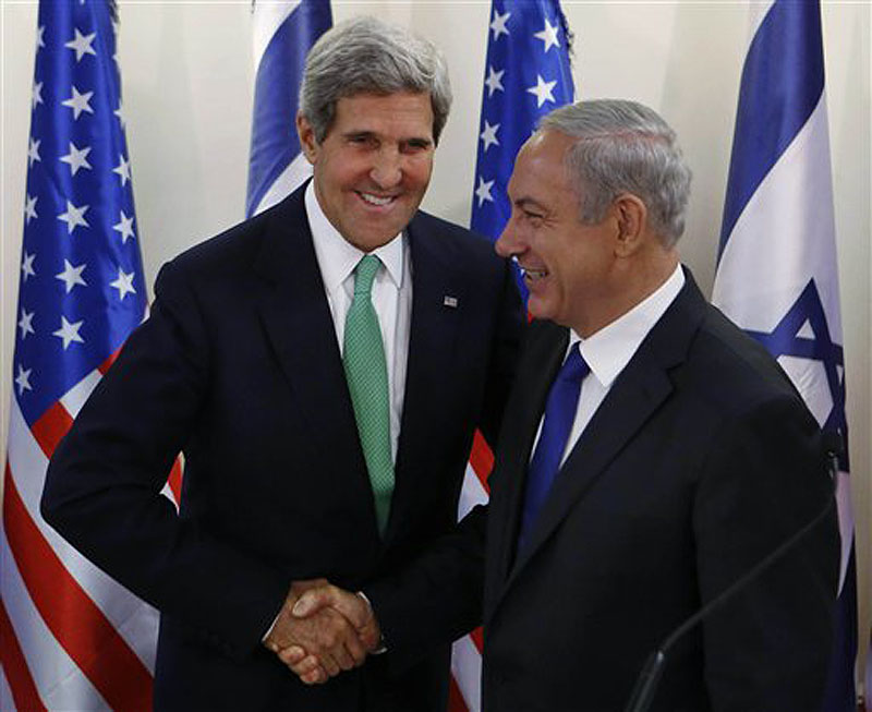 "Secretary of State John Kerry shakes hands with Israel's Prime Minister Benjamin Netanyahu at the prime minister's office in Jerusalem on Sunday. Kerry sent a strong warning to Syria on Sunday, saying ""the threat of force is real"" if Syria does not carry out an internationally brokered agreement to hand over its chemical weapons. POOL PHOTO"