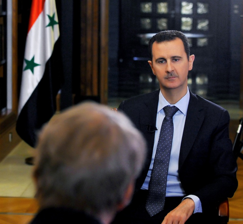 """In this Sunday, Sept. 8, 2013 photo released by the Syrian official news agency SANA, PBS host Charlie Rose, foreground, interviews Syrian President Bashar Assad at the presidential palace in Damascus, Syria. In an interview broadcast Monday, Sept. 9, 2013 on """"CBS This Morning,"""" Assad denied responsibility and accused the Obama administration of spreading lies without providing a """"single shred of evidence,"""" he warned that air strikes against his nation could bring retaliation. (AP Photo/SANA)"""