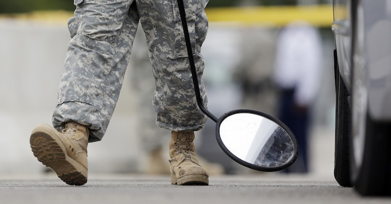 """In this Aug. 27, 2013 file photo, a mirror is used on a vehicle at a security checkpoint to enter the Lawrence William Judicial Center as the sentencing phase for Maj. Nidal Hasan continues in Fort Hood, Texas. Hasan was convicted of killing 13 of his unarmed comrades in the deadliest attack ever on a U.S. military base. The rampage Monday, Sept. 16, 2013, at the Washington Naval Yard shocked the military, just as the attack at Fort Hood did. Defense Secretary is ordering a review of base security worldwide, and the issuing of security clearances that allow access to them, vowing: """"Where there are gaps, we will close them."""" (AP Photo/Eric Gay, File)"""