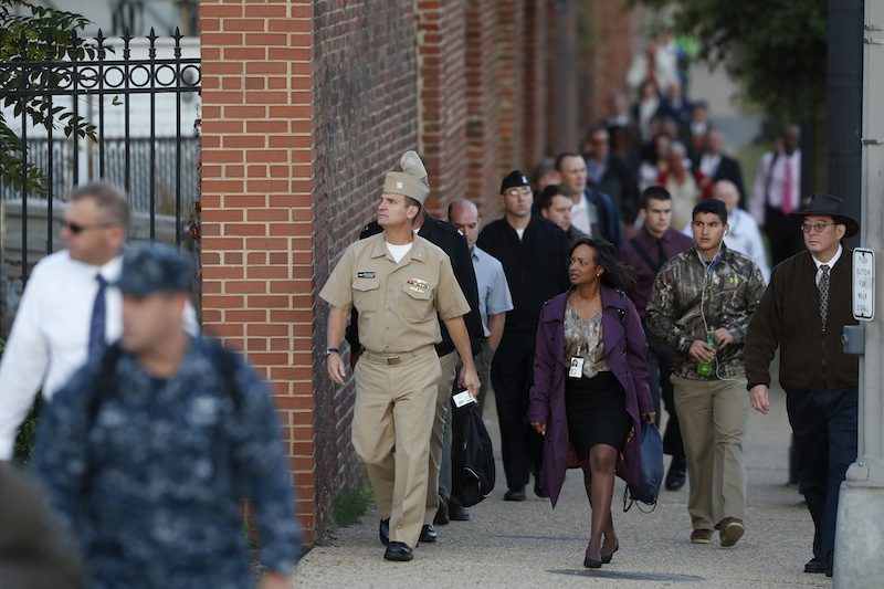 Military personnel and workers walk along the perimeter of the Washington Navy Yard Thursday, Sept. 19, 2013. The Washington Navy Yard began returning to nearly normal operations three days after it was the scene of a mass shooting in which a gunman killed 12 people. (AP Photo/Charles Dharapak)