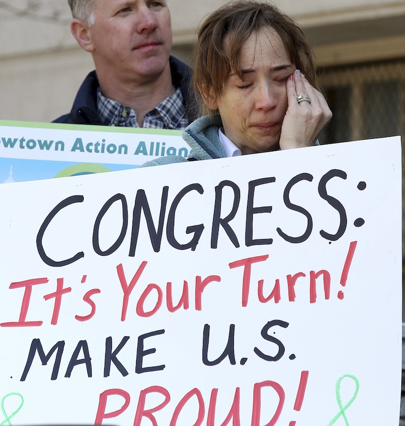 In a Friday, April 5, 2013 file photo, Newtown, Conn., resident Jennifer Killin wipes tears on the steps of Hartford, Conn., City Hall, during a rally to urge passage of federal legislation to curb gun violence. Activists from Newtown, where 26 people were gunned down in a mass shooting at an elementary school in December 2013, headed to Washington on Tuesday, Sept. 17, 2014 to lobby again for gun control. The trip was planned to mark roughly nine months since the Dec. 14 rampage, but took on new urgency in the wake of the massacre in the capital that killed 13 on Monday. (AP Photo/Journal Inquirer, Jared Ramsdell, File) MANDATORY CREDIT
