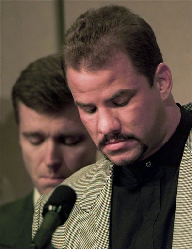 """FILE - In this Feb. 15, 1996 file photo, heavyweight boxer Tommy Morrison, right, and promoter Tony Holden bow their heads during an emotional moment at a news conference about Morrison being HIV positive, in Tulsa, Okla. Morrison, a former heavyweight champion who gained fame for his role in the movie """"Rocky V,"""" has died. He was 44. Holden says his longtime friend died Sunday night, Sept. 1, 2013, at a Nebraska hospital."""