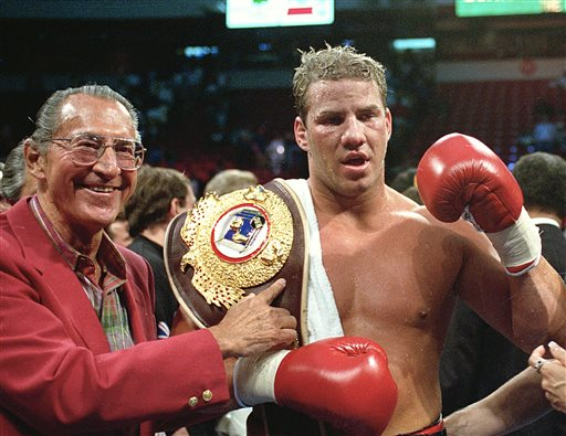 """In this June 7, 1993 file photo, newly crowned WBO heavyweight champion Tommy Morrison receives his championship belt after defeating George Foreman in Las Vegas, Nev. Morrison, a former heavyweight champion who gained fame for his role in the movie """"Rocky V,"""" has died. He was 44. Morrison's former manager, Tony Holden says his longtime friend died Sunday night, Sept. 1, 2013, at a Nebraska hospital."""