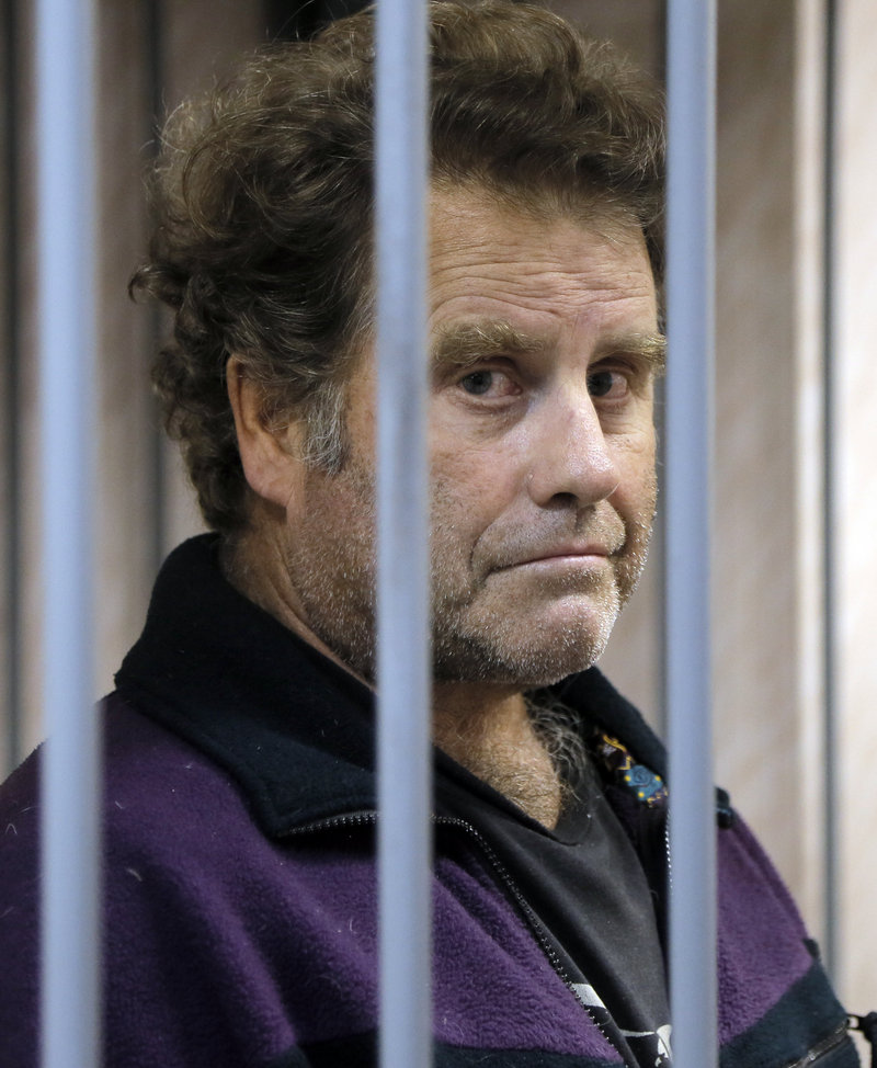 Peter Willcox, the captain of the Greenpeace ship Arctic Sunrise, is kept behind bars in a courtroom in Murmansk, Russia, on Thursday.