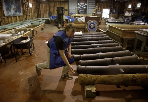 Chris Macort, a field archaeologist working with the Whydah pirate ship museum, reaches down to check one of the ship's cannons at the museum's warehouse in Brewster, Mass. The Whydah sank in a brutal storm in 1717 with plunder from 50 ships.