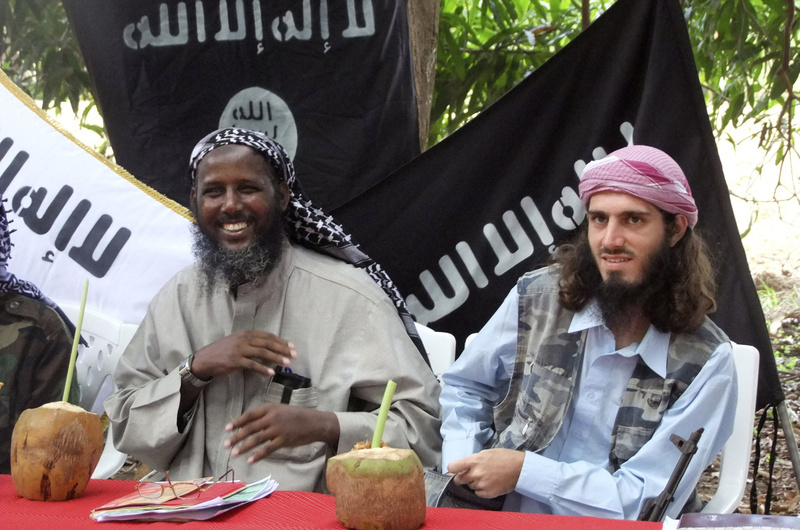 "American-born Islamist militant Omar Hammami, right, and deputy leader of al-Shabab Sheik Mukhtar Abu Mansur Robow sit under a banner that reads ""Allah is Great"" during a news conference of the militant group in Somalia in May 2011. Hammami was killed Thursday in an ambush ordered by the militant group's leader, militants said."