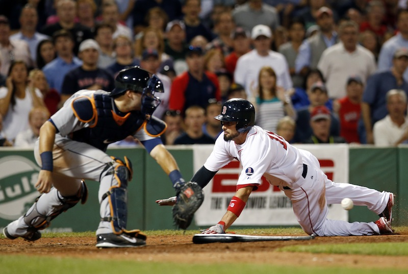 Boston Red Sox's Shane Victorino slides into home plate, beating the throw into Detroit Tigers catcher Alex Avila, to score by tagging up on a fly ball by Dustin Pedroia in the fifth inning of a baseball game at Fenway Park in Boston, Wednesday, Sept. 4, 2013. (AP Photo/Elise Amendola)