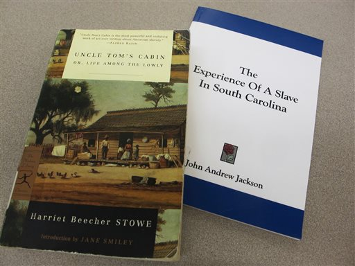"""Copies of Harriet Beecher Stowe's """"Uncle Tom's Cabin"""" and John Andrew Jackson's """"The Experience of a Slave in South Carolina"""" are seen in this Aug. 29, 2013 photo taken at the Charleston County Library in Charleston, S.C. A professor of American literature at Clemson University, Susanna Ashton, says her research indicates Stowe harbored Jackson, then a fugitive slave, in her Maine home just before she started writing her novel """"Uncle Tom's Cabin."""" Ashton says Jackson shared his painful experiences of slavery prompting Stowe to write the novel."""