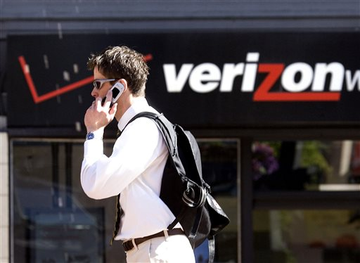In this Monday, July 28, 2008, file photo, Eric Roden speaks on his cell phone as he walks past a Verizon store in Portland, Ore. Verizon says, Monday, Sept. 2, 2013, it has agreed to buy Vodafone's stake in Verizon Wireless for $130 billion.