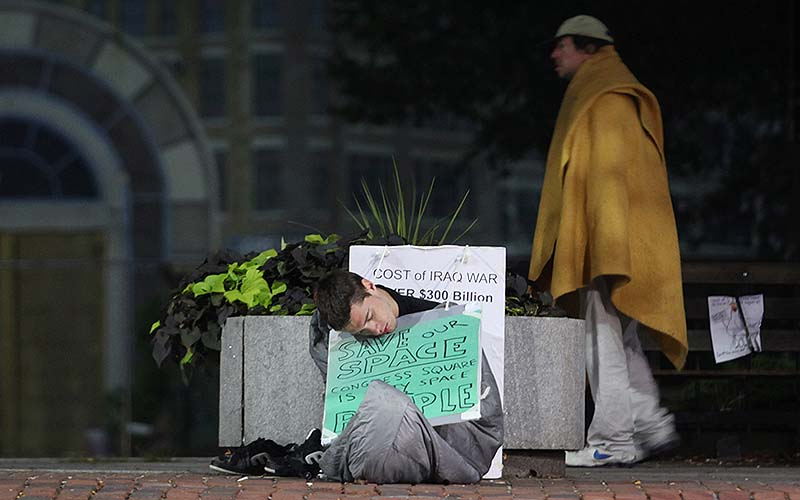 "Protester ""Ares"" of Portland, sleeps on the sidewalk in front of Congress Square Plaza before sunrise Saturday in Portland. ""Ares"" vowed to stay in the plaza through the weekend to protest the sale of the public space."