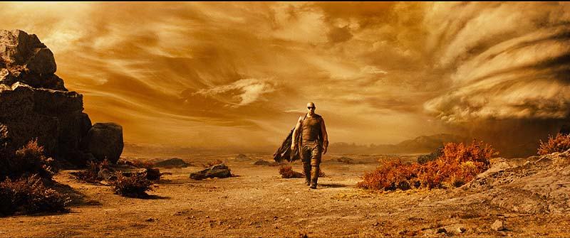 Vin Diesel as Riddick explores the desert planet on which he has been stranded.